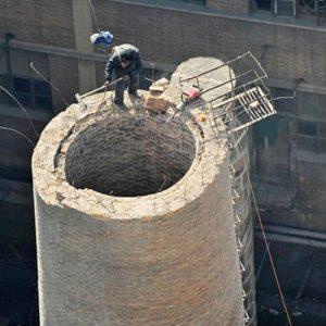 Operario subido a una chimenea de ladrillo